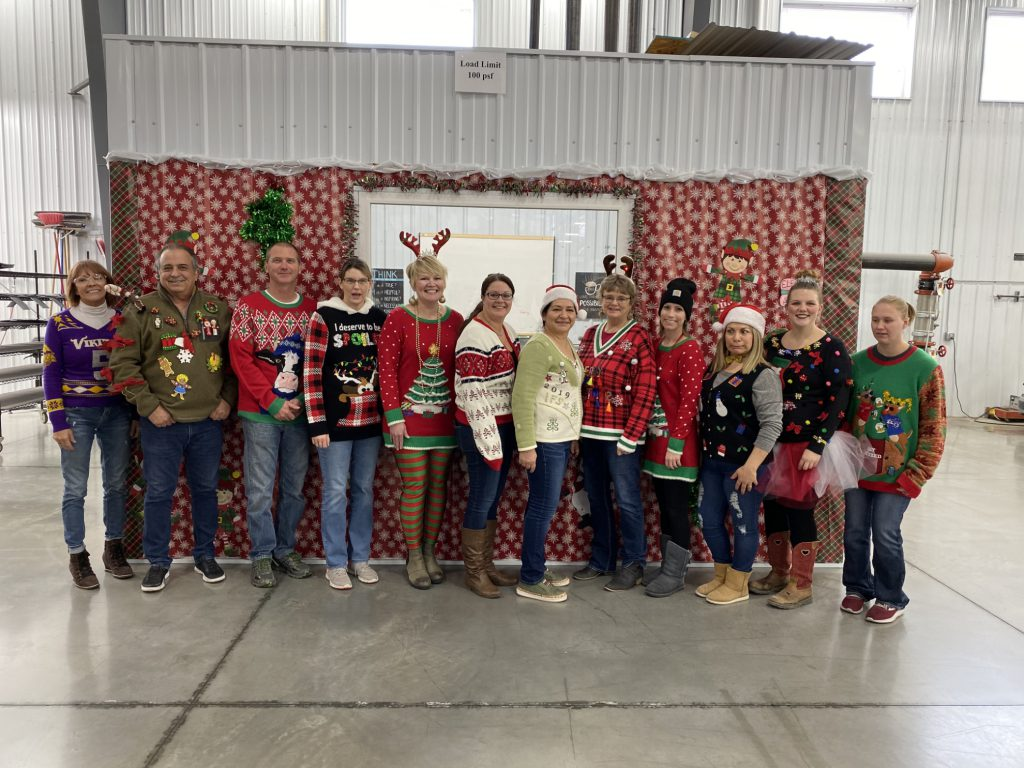 Picture of a dozen IFS employees dressed up in ugly sweaters for Christmas